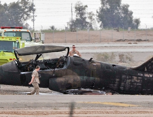 Officials check the scene of a T-59 Hawk aircraft crash Wednesday, March 11, 2015, at the Marine Corps Air Station in Yuma, Ariz. Marine Corps officials say a Marine has died after the aircraft operated by a civilian crashed on the runway. (AP Photo/The Yuma Sun, Randy Hoeft)