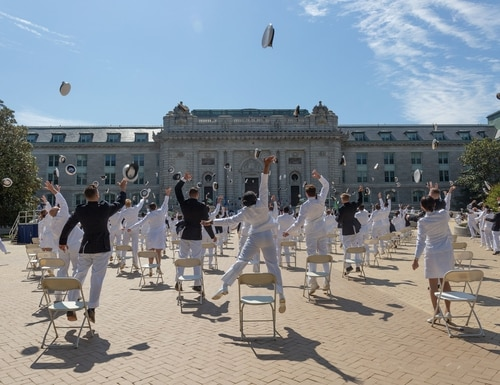 Midshipmen toss their covers May 14, 2020, concluding the second swearing-in event for the United States Naval Academy Class of 2020 in Annapolis, Md. (Stacy Godfrey/Navy)