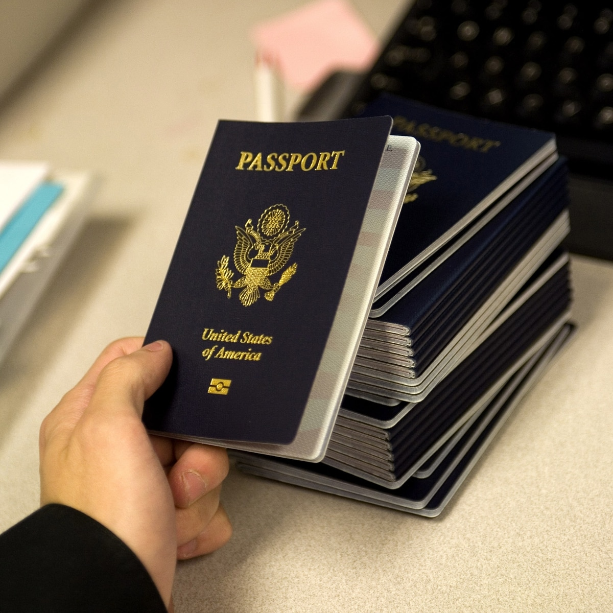 (files) A Us Government Official With The State Department's Passport  Services Reaches For A New Blank Us Passport With An Embedded Electronic  Chip To Begin