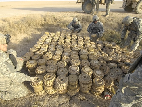 Soldiers of the 789th Ordnance Company prepare a cache of landmines, mortars, and 107mm rockets to be disposed of by a high explosives charge, near Besmaya Region Southeast of Baghdad, Iraq. Army researchers are designing smarter, safer and more mobile landmines for future operations. (Army)
