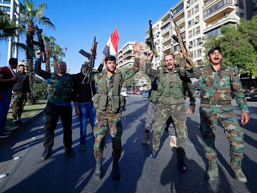 Syrian soldiers hold their weapons as they dance and chant slogans against U.S. President Trump during demonstrations following a wave of U.S., British and French military strikes to punish President Bashar Assad for suspected chemical attack against civilians, in Damascus, Syria, Saturday, April 14, 2018. Hundreds of Syrians are demonstrating in a landmark square in the Syrian capital, waving victory signs and honking their car horns in a show of defiance. (Hassan AmmarAP)