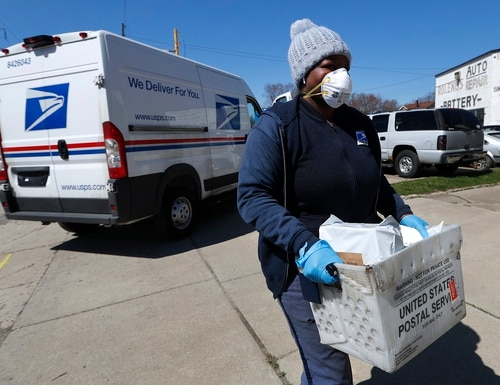 In this April 2, 2020, file photo, a United States Postal Service worker makes a delivery with gloves and a mask in Warren, Mich. (Paul Sancya/AP)