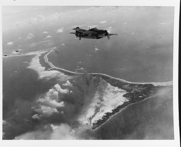 FM-1 Wildcat fighters from the aircraft carrier Corregidor fly over Butaritari Island, Makin Atoll, the during pre-invasion bombardment, 20 November 1943. Photo looks to the east, with Flink Point in lower center and beach