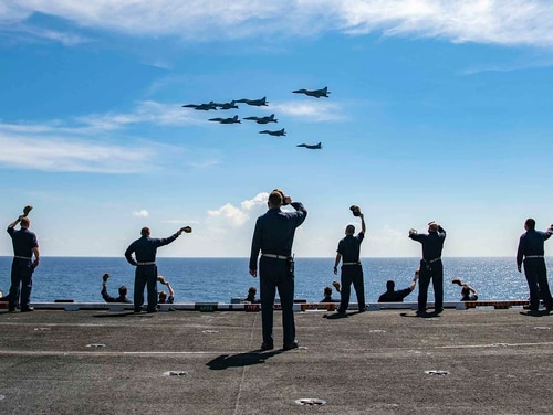 Master Chief David Conduff, command master chief of the aircraft carrier Nimitz, waves to four F/A-18s from the Nimitz and four MiG 29K Fulcrum K from the Indian navy aircraft carrier INS Vikramaditya on Nov. 20, 2020, from the flight deck of the Nimitz while participating in Malabar 2020 in the Indian Ocean. (MC3 Charles DeParlier/Navy)