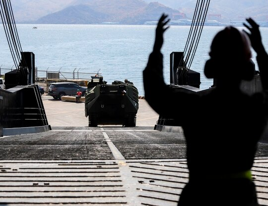 Marine Corps Cpl. Romarion Ferguson-Coleman ground-guides an assault amphibious vehicle onto the USNS Pililaau (T-AKR-304) April 23, 2019, at Subic Bay, Republic of the Philippines. (Lance Cpl. Mark Fike/Marine Corps)