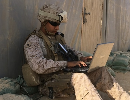 Staff Sgt. Jose Flores working on his doctorate class after getting off a 10-hour convoy in Iraq. (Staff. Sgt. Jose Flores)