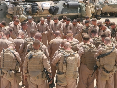A Navy Chaplain leads U.S. Marines with 1st platoon, Alpha Company, 2nd Light Armored Reconnaissance, Task Force Mech, in a moment for prayer before they head out on missions at Haditha Dam, Iraq, on May 10, 2008. 2nd LAR, Task Force Mech, Ground Combat Element, Multi National Force - West is conducting operations along the northern boundary of Al Anbar Province in support of Operation Defeat Al Qaida in the North. (U.S Marine photo/Sgt. Rome M. Lazarus)