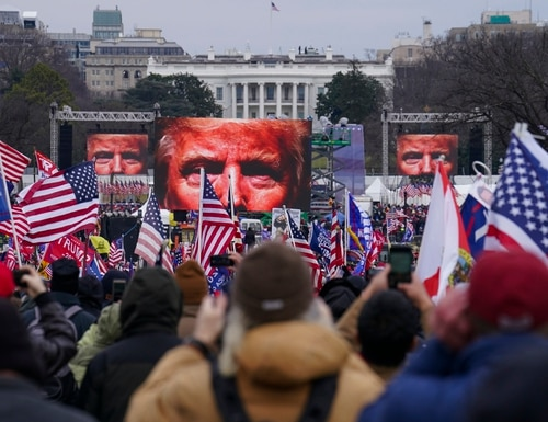 A video posted on the internet showed Mark Sami Ibrahim carrying a flag bearing the words 'Liberty or Death' outside the Capitol, about 12 minutes before a mob of people pulled apart a nearby set of barricades. (John Minchillo/AP)