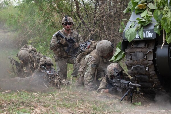 U.S. soldiers with 1st Stryker Brigade Combat Team, 7th Infantry Division, take cover behind a Philippine armored personnel carrier in a simulated assault during Balikatan 2019 at Camp O'Donnell, Philippines. (Sgt. Ariel J. Solomon/Army)