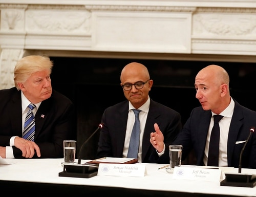 President Donald Trump, left, and Satya Nadella, Microsoft CEO, center, listen as Jeff Bezos, Amazon CEO, speaks during an American Technology Council roundtable at the White House on June 19, 2017. (Alex Brandon/AP)