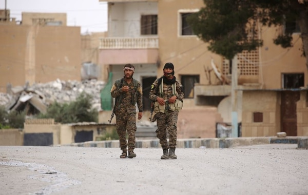 Members of the Syrian Democratic Forces (SDF), walk in the town of Tabqa, about 55 kilometres (35 miles) west of Raqa city, on May 18, 2017. On November 5, 2016, a US-backed alliance of Kurdish and Arab fighters began an operation to capture IS' de facto Syrian capital. On May 10, 2017, the SDF captured the city of Tabqa and an adjacent dam, the last big town before Raqa. / AFP PHOTO / DELIL SOULEIMAN (Photo credit should read DELIL SOULEIMAN/AFP/Getty Images)