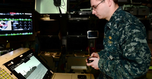 In this Feb. 2, 2018, photo released by the U.S. Navy, Lt. j.g. William Gregory uses an Xbox game controller to maneuver the photonics mast aboard the submarine scheduled to be commissioned as the USS Colorado on Saturday, March 17, 2018, in Groton, Conn. (Steven Hoskins/U.S. Navy via AP)