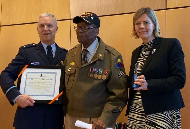 Dr. James W. Baldwin, a corporal who served in the 784th Tank Battalion, receives a certificate from Air Commodore Paul Herber and Deputy Chief of Mission Heleen Bakker at the Dutch Embassy on Feb. 6, 2020. (Courtesy of the Embassy of the Kingdom of the Netherlands/Jeffrey Allanach)