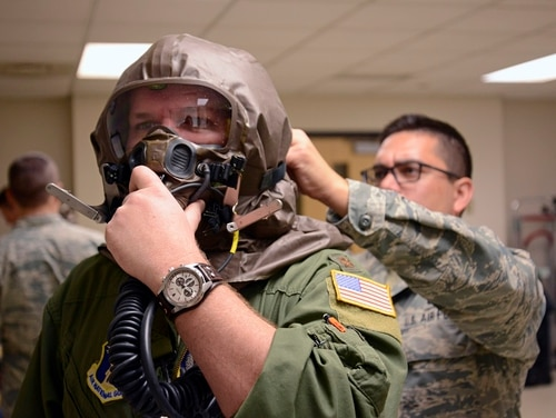 Master Sgt. Ricky Carrillo assists Maj. Daniel Hale with donning his aircrew eye and respiratory protection system (AERPS) equipment during training. A group of airmen at Yokota Air Base have developed an alternative to AERPS that has the potential to save the Air Force millions of dollars. (Tech. Sgt. Amber Monio/Air National Guard)