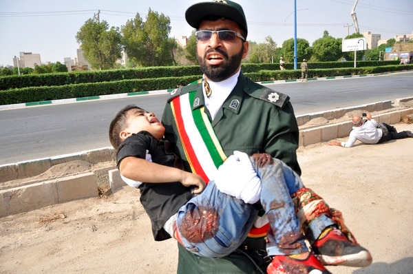 A Revolutionary Guard member carries a wounded boy after a shooting during a military parade marking the 38th anniversary of Iraq's 1980 invasion of Iran, in the southwestern city of Ahvaz, Iran, on Saturday. (Behrad Ghasemi/ISNA via AP)