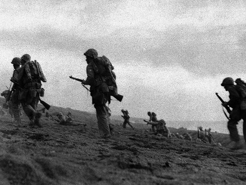 Original caption from 1945: Without a scrap of cover in sight, U.S. Marines plod through volcanic sand as they start their advance inland in the bloodiest of their battles, on Iwo Jima, March 2, 1945. Their third airfield on Iwo and the end of the battle is not far off. (AP Photo/INP/Paige Abbott)