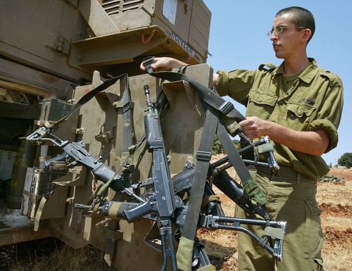 KIBBUTZ YIFTAH, ISRAEL - AUGUST 11: An Israeli soldier hangs his Galil assault rifle on the back door of a 155mm mobile artillery piece as a battery of Israel's heavy guns deploys August 11, 2003 in the fields of Kibbutz Yiftah on the Israeli-Lebanese border. Israel warned Syria if the pro-Iranian Hezbollah militia continue their attacks against northern Israel, it would respond against Syrian targets in Lebanon. A 16-year-old Israeli youth was killed and four more Israelis wounded when a Hezbollah anti-aircraft shell landed in the border town of Shlomi yesterday. (Photo by David Silverman/Getty Images)