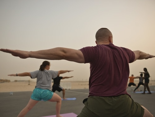Deployed Soldiers, sailors, airmen, Marines, coalition partners and civilians go into the Warrior Two pose during the largest Yoga session to take place in Qatar history July 11, 2015 at Al Udeid Air Base, Qatar. This event opened its doors to all levels of practitioners from novice to expert. It allowed the fine men and women assigned to Al Udeid Air Base to relax and enjoy a different kind of exercise in a neutral environment. (U.S. Air Force photo/Staff Sgt. Alexandre Montes)