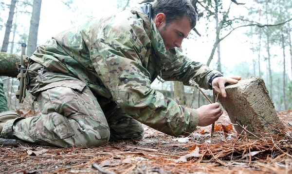 A student from the U.S. Army John F. Kennedy Special Warfare Center and School practices setting a paiute deadfall trap for small game during the survival phase of Survival Evasion Resistance and Escape Level-C training (SERE) at Camp Mackall, N.C., Feb. 28, 2019. (Ken Kassens/U.S. Army via AP)