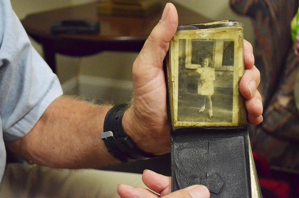 In this July 21, 2017, photo, a wallet belonging to World War II soldier Ira G. Royster is displayed with a photo of his daughter Catherine Royster Corpening, in High Point, N.C. (Stephanie Butzer/The High Point Enterprise via AP)