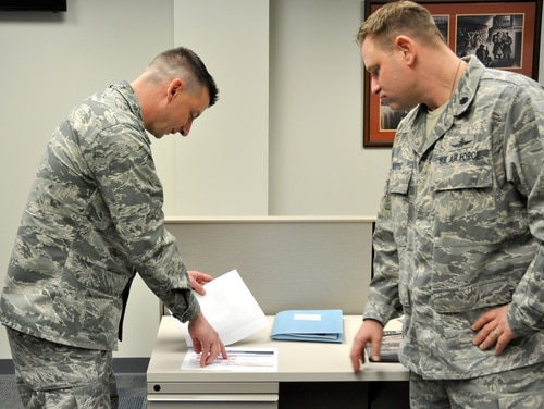 U.S. Transportation Command's Lt. Col. John Riester (left) and Lt. Col. Ross Morrell, review a briefing for leaders on the next steps the command will take as it moves forward with its transition to cloud computing. (Photo by Maj. Nichole L Downs)