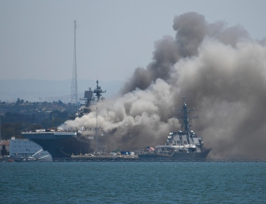 Smoke rises from the USS Bonhomme Richard at Naval Base San Diego Sunday, July 12, 2020, in San Diego after an explosion and fire Sunday on board the ship at Naval Base San Diego. (Denis Poroy/AP)