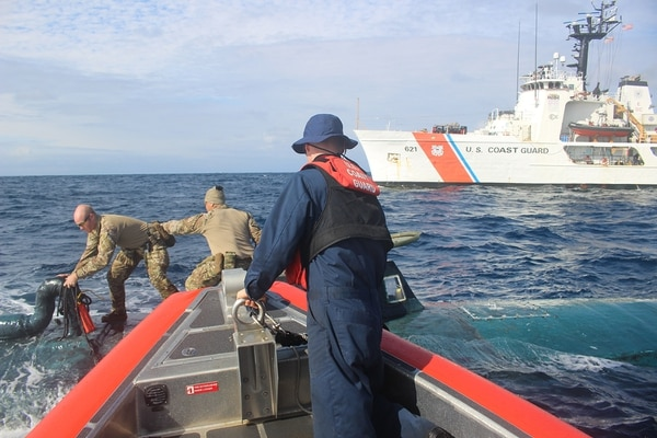 Members of a boarding team from the Coast Guard cutter Valiant transfer narcotics from a suspected smuggling vessel in September. (Coast Guard)