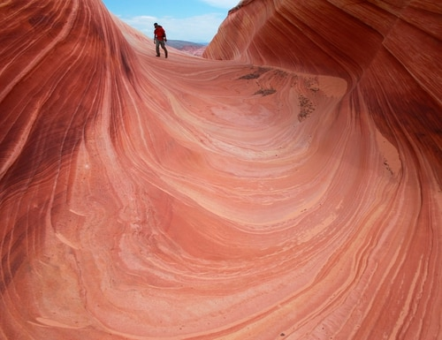 FILE - In this May 28, 2013, file photo, a hiker walks on a rock formation known as The Wave in the Vermilion Cliffs National Monument in Arizona. Interior Secretary Ryan Zinke said he's recommending that none of 27 national monuments carved from wilderness and ocean and under review by the Trump administration be eliminated, including the Vermilion Cliffs National Monument. (AP Photo/Brian Witte, File)