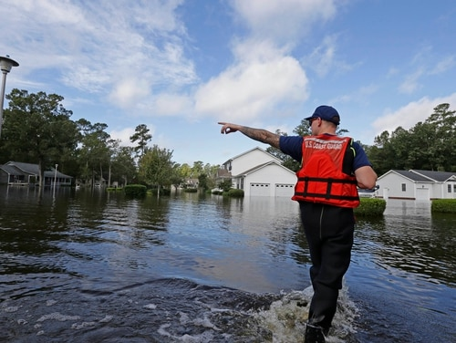 U.S. Coast Guard Petty Officer Second Class Don Tantanella checks on a flooded neighborhood in Lumberton, N.C., Monday, Sept. 17, 2018, following flooding from Hurricane Florence. (Gerry Broome/AP)