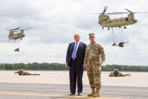President Donald Trump, left, seen here with Maj. Gen. Walter Piatt, commander of the 10th Mountain Division, during an August trip, appeared to call for cuts to the Defense Department's budget. (Sgt. Thomas Scaggs/U.S. Army)