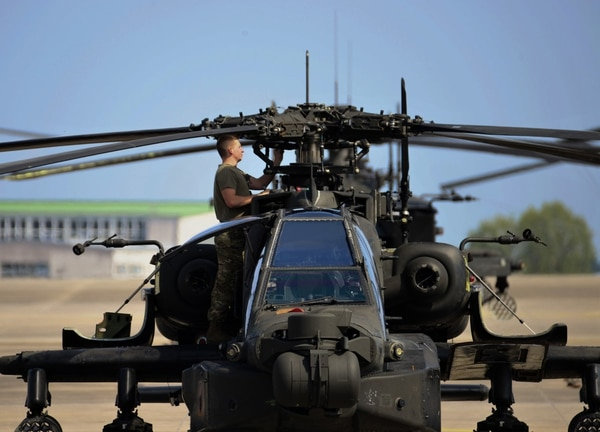 An American soldier with the 12th Combat Aviation Brigade conducts routine maintenance on a AH-64 Apache helicopter at Katterbach Army Airfield in Germany. (Charles Rosemond/U.S. Army)