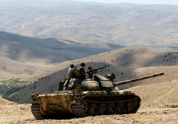 A picture taken on Aug. 2, 2017, during a tour guided by the Lebanese Shiite Hezbollah movement shows members of the Syrian government forces riding over a tank at a position in a mountainous area around the Syrian town of Flita near the border with Lebanon. (Louai Beshara/AFP/Getty Images)