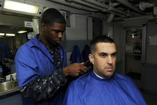Chief Aviation Electronics Technician Kirk P. Killian, shown here getting a haircut in 2010, pleaded guilty to a charge of stealing military gear on July 29 and was bumped down to E-6. (Navy)