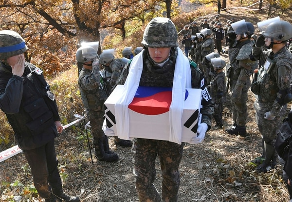 A South Korean soldier carries a coffin containing a piece of bone believed to be the remains of an unidentified South Korean soldier killed in the Korean War in the Demilitarized Zone (DMZ) dividing the two Koreas in Cheorwon, northeast of Seoul, Thursday, Oct. 25, 2018. (Jung Yeon-je/Pool Photo via AP)