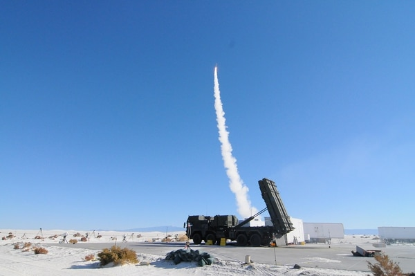 A MEADS launcher sits ready while a second fires a missile in the background. (White Sands Missile Range Public Affairs)