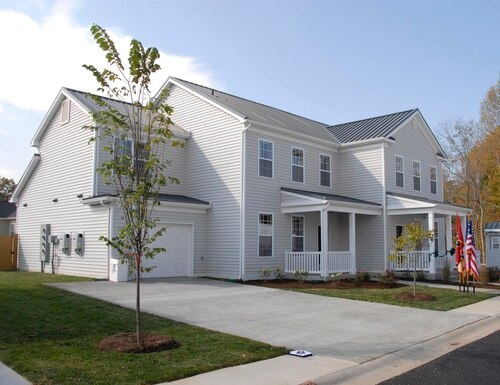 A ribbon-cutting ceremony takes place as Campbell Crossing celebrates the completion of the first two zero-energy homes on a military installation at Fort Campbell, Ky., in 2010. (Army)
