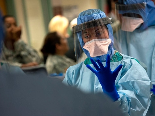 Capt. Stacey Morgan dons protective gloves during infection prevention and control training at the San Antonio Military Medical Center in San Antonio. (Master Sgt. Jeffrey Allen/Air Force)