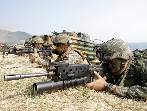 "In this March 30, 2015, file photo, marines of South Korea, right, and the U.S aim their weapons near amphibious assault vehicles during U.S.-South Korea joint landing military exercises as part of the annual joint military exercise Foal Eagle between the two countries in Pohang, South Korea. U.S. President Donald Trump promised to end ""war games"" with South Korea, calling them provocative, after meeting North Korean leader Kim Jong Un on June 12, 2018. His announcement appeared to catch both South Korea and the Pentagon by surprise. (Lee Jin-man/AP)"