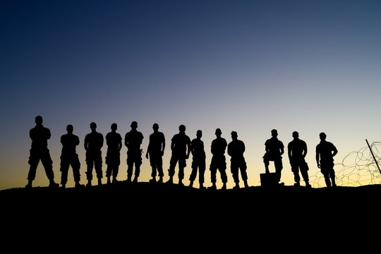 Airmen of the 332nd Air Expeditionary Wing pose for a group photo during sunrise after their shift at an undisclosed location on Aug. 15, 2020. (Master Sgt. Jonathan Young/Air National Guard)