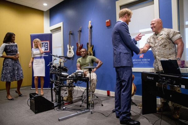 Britain's Prince Harry, second from right, accompanied by first lady Michelle Obama, left, Jill Biden, second from left, and Marine Sgt. Roderic Liggens of Washington, center, greets Marine Col. Shane Tomko as he tours the USO Warrior and Family Center at Fort Belvoir, Va in 2016. The center was a project by the USO Metropolitan Washington-Baltimore, and their CEO is 2018's Honorary Sergeant Major of the Army. (Andrew Harnik/AP)