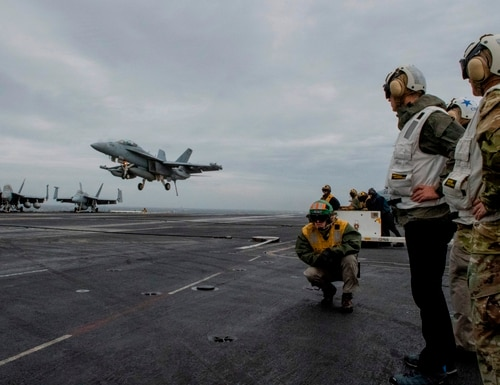 NATO Secretary General, Jens Stoltenberg looks at a F-18 Super Hornet landing on of the US Nimitz-class aircraft carrier USS Harry S. Truman in The North Sea on Oct. 12, 2018. - The aircraft carrier is on its way to the Norwegian coast to participate in the NATO exercise Trident Juncture. (Johan Falnes/AFP/Getty Images)