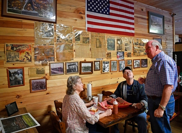 In this Feb. 21, 2018, photo, local residents Janet and Bruce Patton talk with retired Col. Gerald York in a market York owns in Pall Mall, Tenn., where the wall holds articles that recount the exploits of his famous grandfather Alvin C. York, a renowned hero of World War I. His granddad earned the Medal of Honor for heroism in October 1918 near Chatel-Chehery, France. (Larry McCormack/The Tennessean via AP)