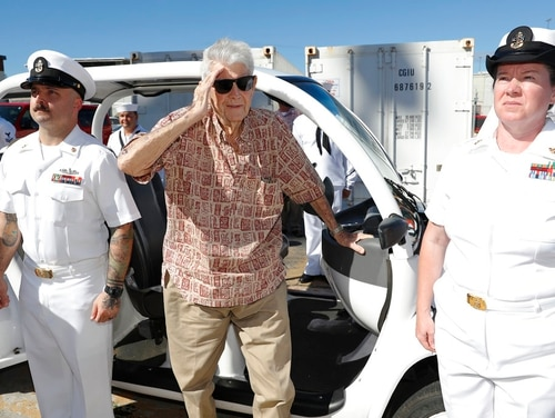 Pearl Harbor survivor Ray Emory, center, salutes sailors who stood in an honor cordon on June 19, 2018, in Honolulu. Emory died Monday, Aug. 20, 2018, in Boise, Idaho, according to his family. (Marco Garcia/AP)