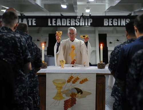 Then-Lt. William Dorwart leads a congregation during a Roman Catholic mass. (Seaman Benjamin C. Jernigan/Navy)