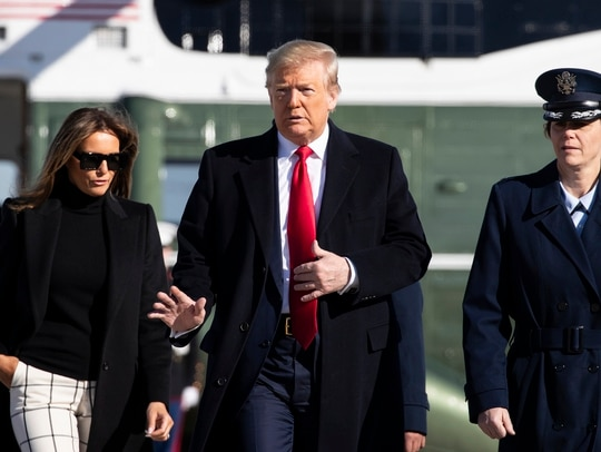 President Donald Trump, with first lady Melania Trump, wave as they walk across the tarmac to board Air Force One during their departure, Sunday, Feb. 23, 2020, at Andrews Air Force Base, Md. Trump is traveling to India. (Alex Brandon/AP)