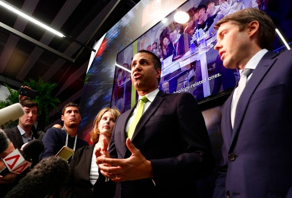 U.S. Deputy Assistant secretary for Cyber and International Communications and Information Policy Robert Strayer, right, and Ajit Pai, chairman of the Federal Communications Commission, centre, attend a press conference at the Mobile World Congress wireless show, in Barcelona on Tuesday. (Manu Fernandez/AP)