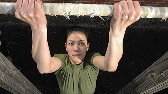Capt. Linda Vong demonstrates pull-ups outside Barber Physical Activity Center aboard Marine Corps Base Quantico, Va., on Friday, March 21, 2014. (Mike Morones/Staff)