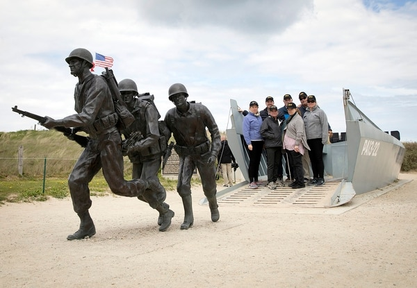 In this May 2, 2019, photo, people stand in a replica landing craft near a statue of WWII U.S. soldiers on Utah Beach in Sainte-Marie-du-Mont, Normandy, France. (Virginia Mayo/AP)