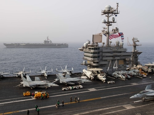 The aircraft carrier Abraham Lincoln, back, sails alongside sister flattop John C. Stennis in the Mediterranean Sea on April 24. (Mass Communication Specialist 3rd Class Grant G. Grady/Navy)