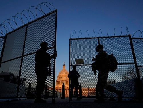 National Guard soldiers open a gate of the razor wire-topped perimeter fence around the Capitol to allow a colleague in on March 8. (Carolyn Kaster/AP)